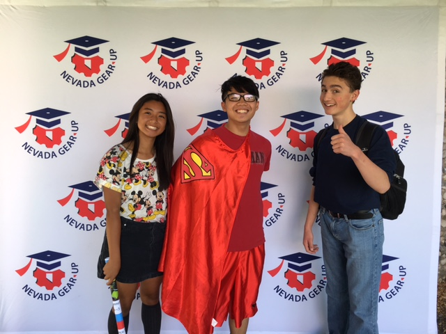 Smiling students, one of them wearing a Superman cape, pose for the camera at Gear Up week