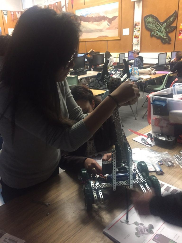 Students carefully apply the finishing touches to a robotic rover