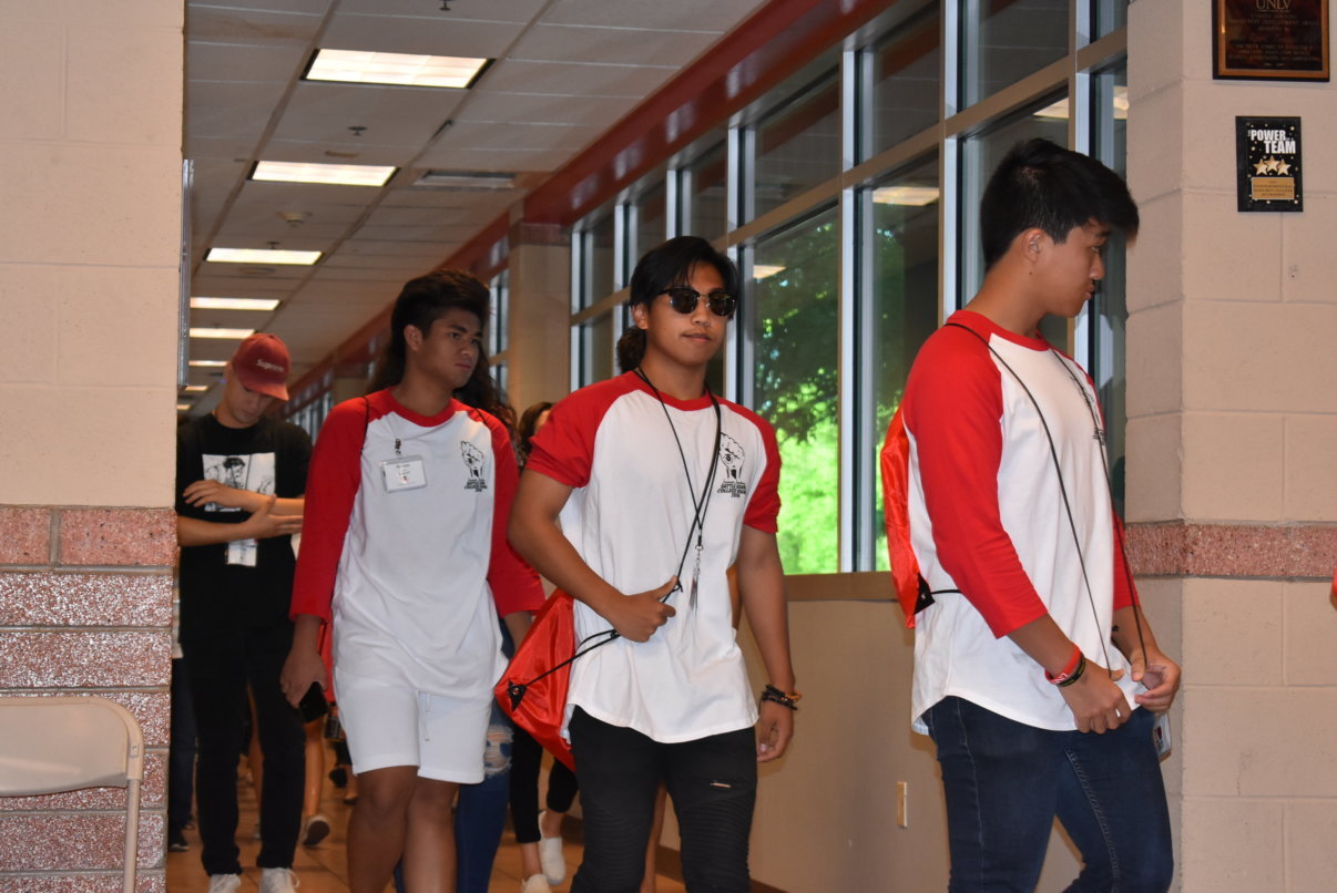 A group of four men walk through a school hallway. The three in the lead are wearing matching baseball tees with red sleeves.