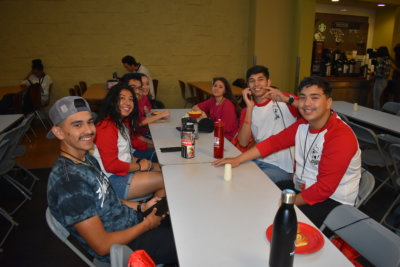 A group of young people, most of them wearing baseball tees with red sleeves, sit at a long cafeteria table and turn to smile at the camera.