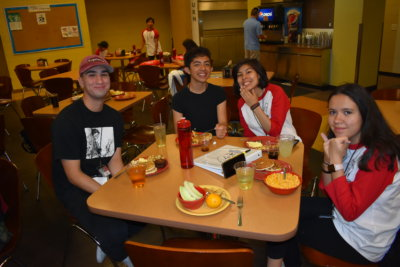 A group of young people sitting at a cafeteria table smile and pose for the camera. Two women are wearing baseball tees with red sleeves, and two men wear black shirts