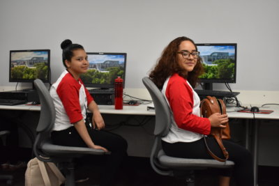 A pair of women wearing baseball tees with red sleeves sit at a bank of computers. They are turned away from the computers to smile for the camera.