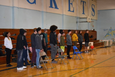 Groups of two to three students each stand behind a folding chair. A red balloon rests on one of the chairs.