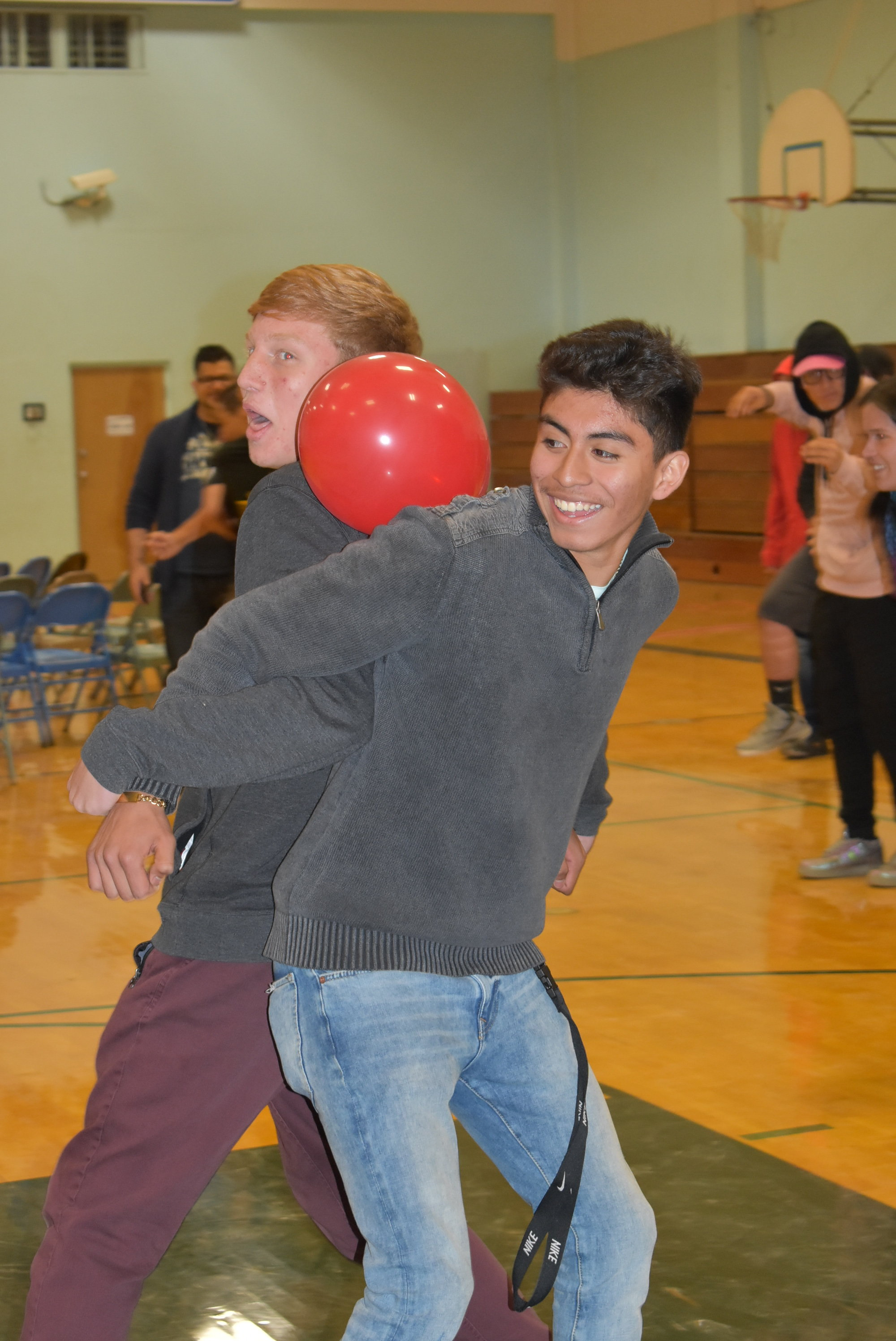Two students standing back to back with their arms linked look on as a red balloon balances precariously between their backs. One student grins while the other carries a look of concerned focus.