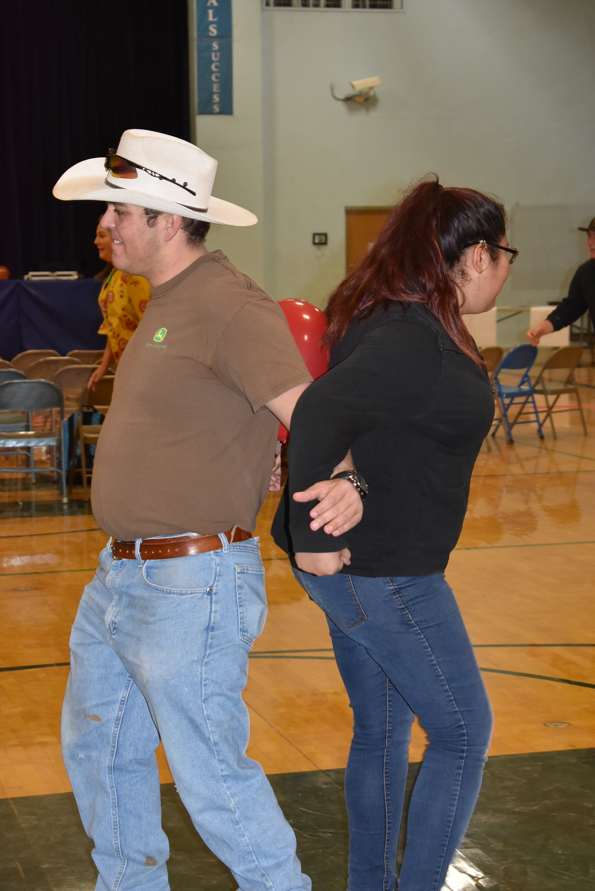 A man in a cowboy hat and a girl in a black sweatshirt stand back to back with their arms linked at the elbow. A red balloon is lodged within the space between their backs.