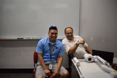 A pair of men sit near a classroom projector and smile for the camera