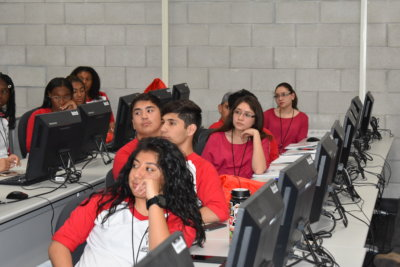 A group of students, all wearing red, sit at computer stations in a computer lab. They are all turned away from the computer monitors with their attention on a presentation.