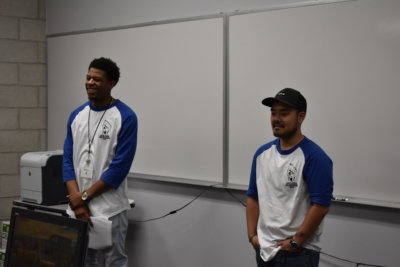 A pair of men wearing baseball tees with blue sleeves stand before a pair of blank whiteboards