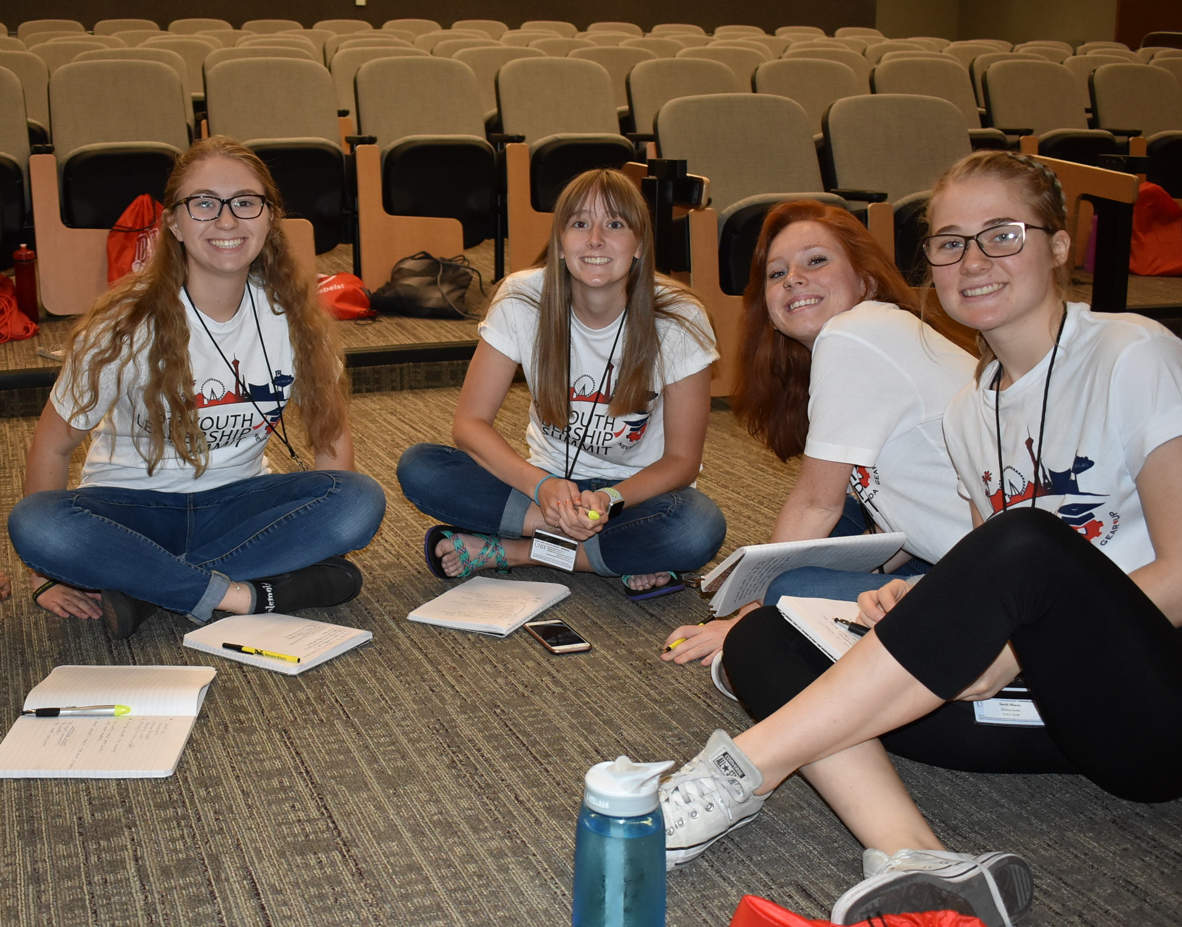 "A group of four young women in matching ""Youth Leadership Summit"" t-shirts sit on an auditorium floor and smile for the camera. Each has a notepad and pen before them."