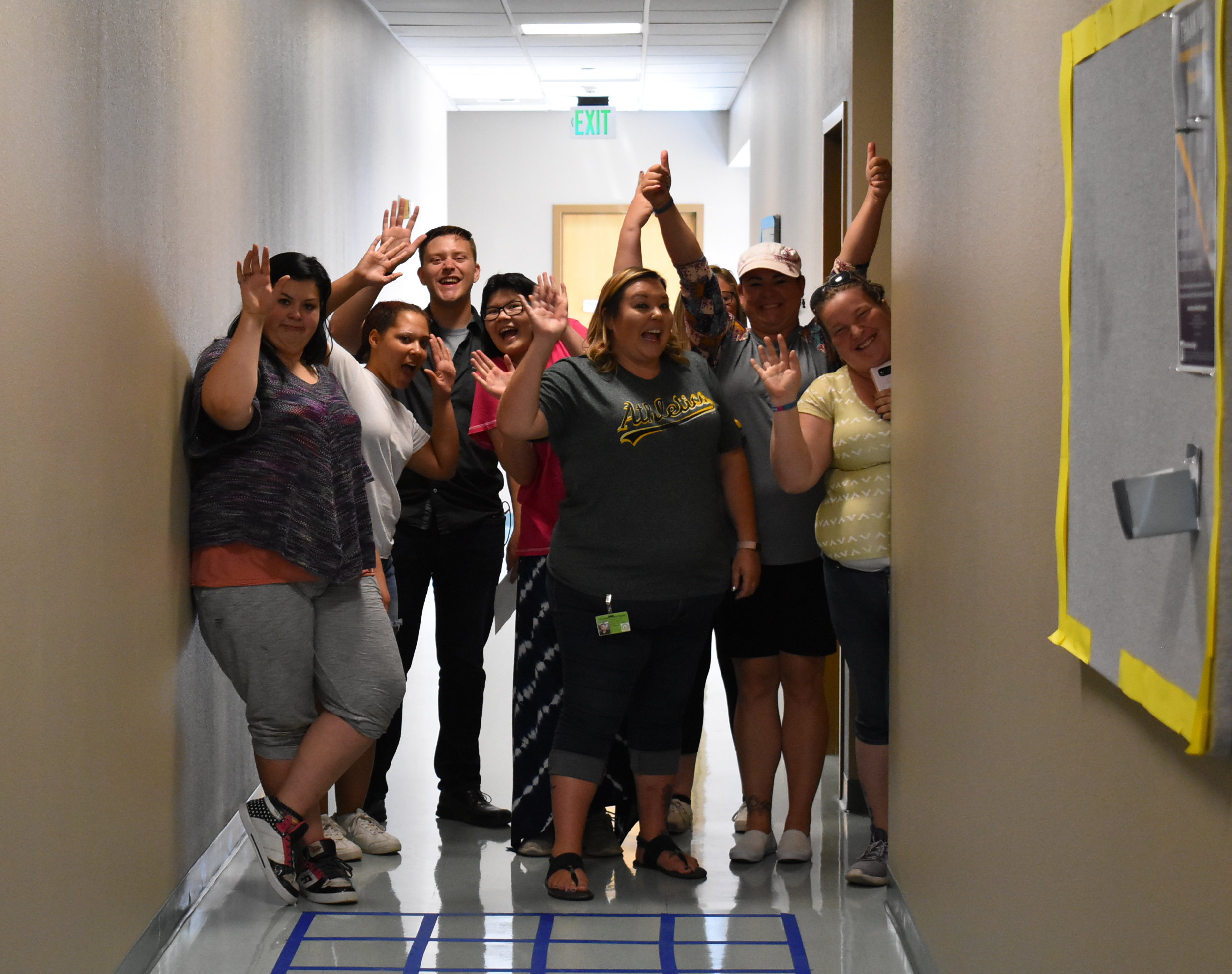A group stands in a school hallway and waves to the camera.