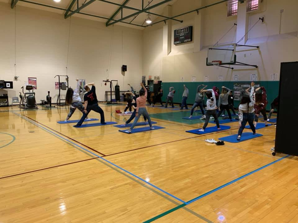 People perform yoga on a basketball court as part of a STEAM workshop.